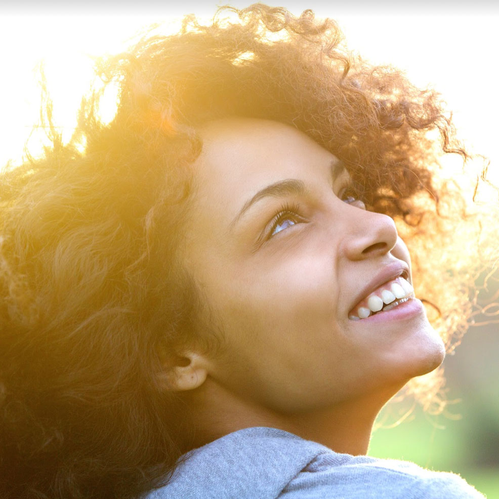 Woman's face smiling with sun behind hair